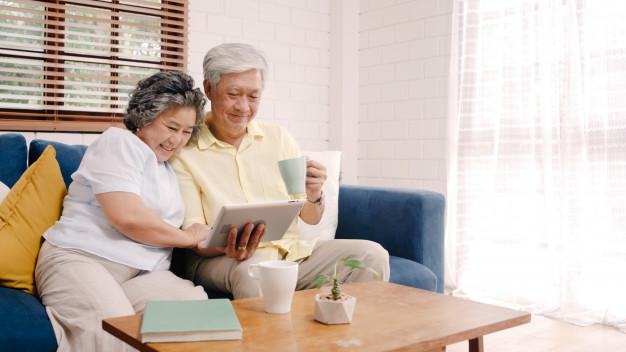 happy-couple-elderly-watching-ipad